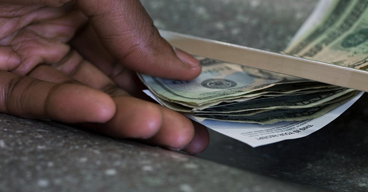Person grabbing money at a bank