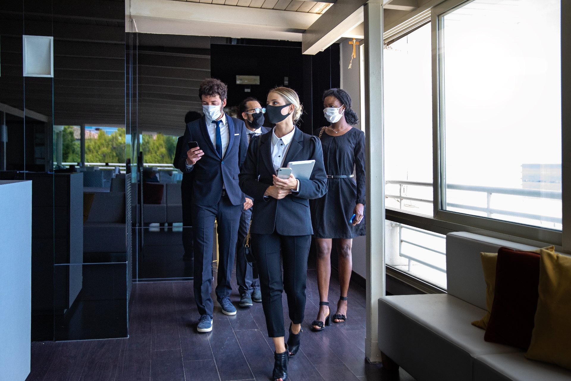 Office employees dressed in black with masks on in an office building